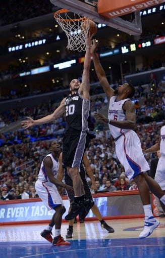 Dec 16, 2013; Los Angeles, CA, USA; San Antonio Spurs guard Manu Ginobili (20) is defended by Los Angeles Clippers center DeAndre Jordan (6) at Staples Center. The Clippers defeated the Spurs 115-92. Mandatory Credit: Kirby Lee-USA TODAY Sports