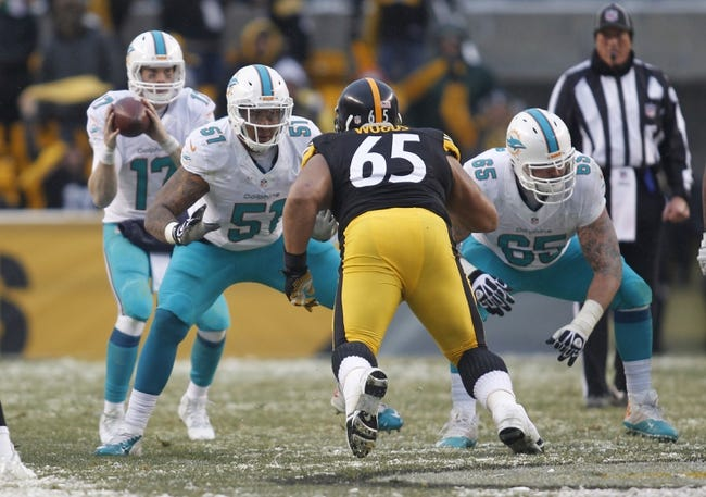 Dec 8, 2013; Pittsburgh, PA, USA; Miami Dolphins center Mike Pouncey (51) and guard Sam Brenner (65) pass block against Pittsburgh Steelers defensive tackle Al Woods (65) during the fourth quarter at Heinz Field. The Dolphins won 34-28. Mandatory Credit: Charles LeClaire-USA TODAY Sports