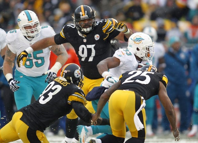 Dec 8, 2013; Pittsburgh, PA, USA; Miami Dolphins running back Daniel Thomas (33) carries the ball as Pittsburgh Steelers outside linebacker Jason Worilds (93) and defensive end Cameron Heyward (97) and free safety Ryan Clark (25) chase during the third quarter at Heinz Field. The Dolphins won 34-28. Mandatory Credit: Charles LeClaire-USA TODAY Sports