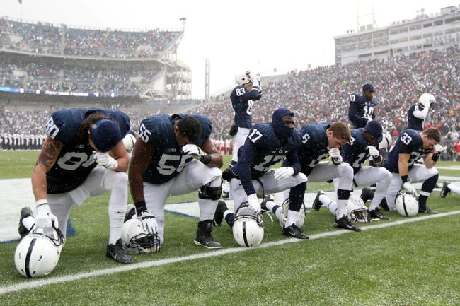Nov 23, 2013; University Park, PA, USA; Penn State Nittany Lions players kneel in the end zone prior to the game against the Nebraska Cornhuskers at Beaver Stadium. Nebraska defeated Penn State 23-20 in overtime. Mandatory Credit: Matthew O'Haren-USA TODAY Sports