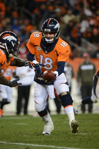 November 17, 2013; Denver, CO, USA; Denver Broncos quarterback Peyton Manning (18) hands the football off during the third quarter against the Kansas City Chiefs at Sports Authority Field at Mile High. The Broncos defeated the Chiefs 27-17. Mandatory Credit: Kyle Terada-USA TODAY Sports