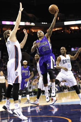 Dec 17, 2013; Charlotte, NC, USA; Sacramento Kings guard Isaiah Thomas (22) drives to the basket as he is defended by Charlotte Bobcats forward Josh McRoberts (11) and guard Kemba Walker (15) during the first half of the game at Time Warner Cable Arena. Mandatory Credit: Sam Sharpe-USA TODAY Sports