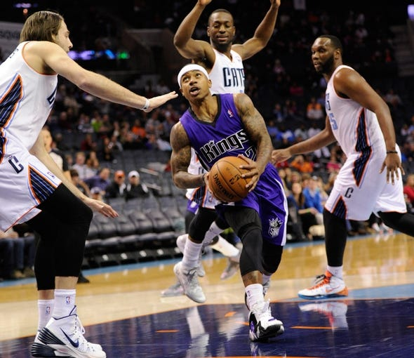 Dec 17, 2013; Charlotte, NC, USA; Sacramento Kings guard Isaiah Thomas (22) drives into the paint against Charlotte Bobcats forward Josh McRoberts (11) guard Kemba Walker (15) and center Al Jefferson (25) during the first half of the game at Time Warner Cable Arena. Mandatory Credit: Sam Sharpe-USA TODAY Sports