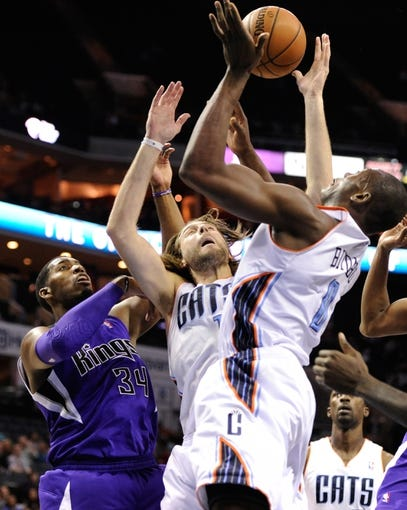 Dec 17, 2013; Charlotte, NC, USA; Charlotte Bobcats forward forward Josh McRoberts (11), forward center Bismack Biyombo (0) and Sacramento Kings forward center Jason Thompson (34) fight for a rebound during the first half of the game at Time Warner Cable Arena. Mandatory Credit: Sam Sharpe-USA TODAY Sports