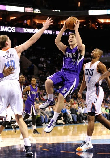 Dec 17, 2013; Charlotte, NC, USA; Sacramento Kings guard Jimmer Fredette (7) drives to the basket as he is defended by Charlotte Bobcats forward Cody Zeller (40) and guard Ramon Sessions (7) during the first half of the game at Time Warner Cable Arena. Mandatory Credit: Sam Sharpe-USA TODAY Sports
