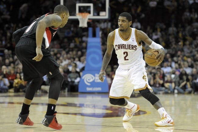 Dec 17, 2013; Cleveland, OH, USA; Cleveland Cavaliers point guard Kyrie Irving (2) dribbles against Portland Trail Blazers point guard Damian Lillard (0) in the fourth quarter at Quicken Loans Arena. Mandatory Credit: David Richard-USA TODAY Sports