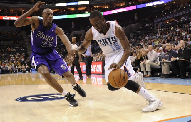 Dec 17, 2013; Charlotte, NC, USA; Charlotte Bobcats guard Kemba Walker (15) drives past Sacramento Kings forward Travis Outlaw (25) during the second half of the game at Time Warner Cable Arena.  Bobcats win 95-87. Mandatory Credit: Sam Sharpe-USA TODAY Sports