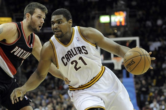 Dec 17, 2013; Cleveland, OH, USA; Cleveland Cavaliers center Andrew Bynum (21) drives against Portland Trail Blazers center Joel Freeland (19) in the fourth quarter at Quicken Loans Arena. Mandatory Credit: David Richard-USA TODAY Sports