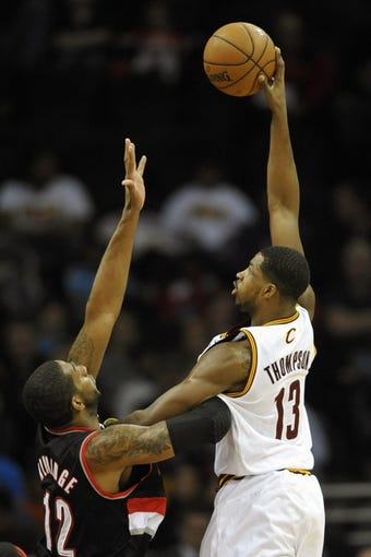 Dec 17, 2013; Cleveland, OH, USA; Cleveland Cavaliers power forward Tristan Thompson (13) shoots over Portland Trail Blazers power forward LaMarcus Aldridge (12) in the first quarter at Quicken Loans Arena. Mandatory Credit: David Richard-USA TODAY Sports