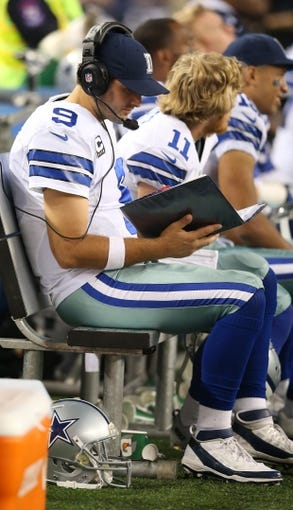 Dec 15, 2013; Arlington, TX, USA; Dallas Cowboys quarterback Tony Romo (9) reads play formation photos while on the bench against the Green Bay Packers at AT&T Stadium. Mandatory Credit: Matthew Emmons-USA TODAY Sports