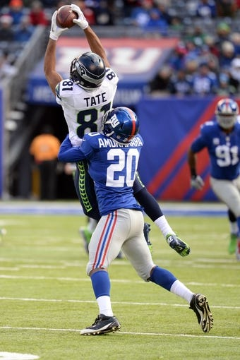 Dec 15, 2013; East Rutherford, NJ, USA; Seattle Seahawks wide receiver Golden Tate (81) makes a catch over New York Giants cornerback Prince Amukamara (20) at MetLife Stadium. The Seahawks won the game 23-0. Mandatory Credit: Joe Camporeale-USA TODAY Sports