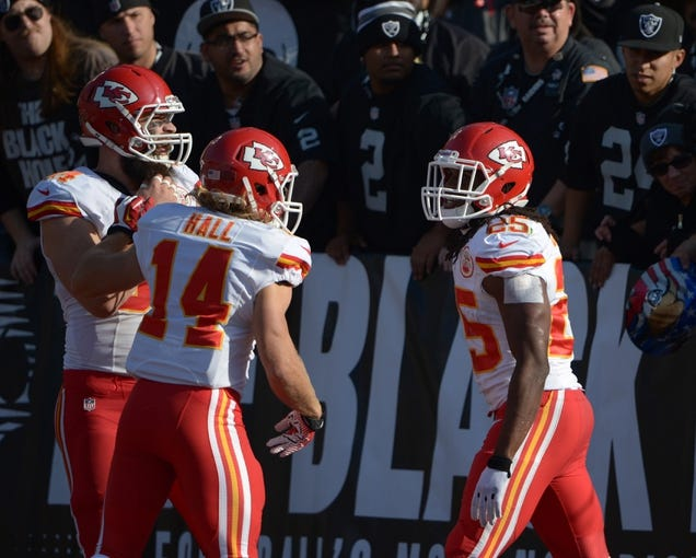 Dec 15, 2013; Oakland, CA, USA; Kansas City Chiefs running back Jamaal Charles (25) celebrates with tight end Sean McGrath (84) and receiver Chad Hall (14) after scoring on a 39-yard touchdown reception in the first quarter against the Oakland Raiders at O.co Coliseum. The Chiefs defeated the Raiders 56-31. Mandatory Credit: Kirby Lee-USA TODAY Sports