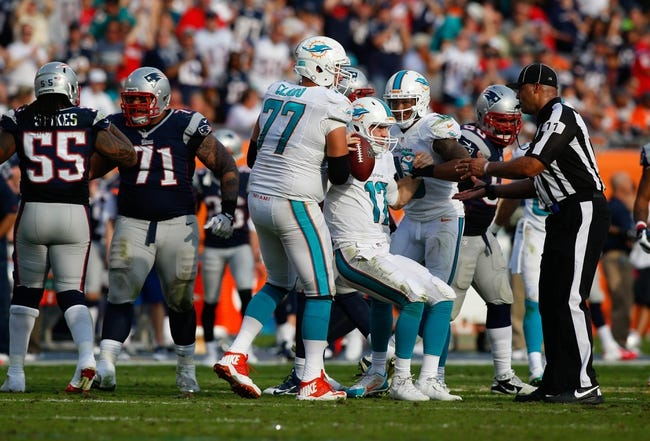 Dec 15, 2013; Miami Gardens, FL, USA: Miami Dolphins quarterback Ryan Tannehill (17) is helped to his feet by tackle Tyson Clabo (77) and wide receiver Rishard Matthews (18) after a sack by the New England Patriots in the second half at Sun Life Stadium. The Dolphins won 24-20. Mandatory Credit: Robert Mayer-USA TODAY Sports