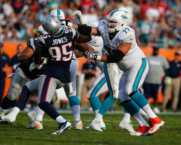 Dec 15, 2013; Miami Gardens, FL, USA: Miami Dolphins tackle Tyson Clabo (77) blocks New England Patriots defensive end Chandler Jones (95) in the second half at Sun Life Stadium. The Dolphins won 24-20. Mandatory Credit: Robert Mayer-USA TODAY Sports