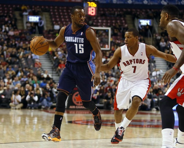 Dec 18, 2013; Toronto, Ontario, CAN; Charlotte Bobcats guard Kemba Walker (15) dribbles the ball against Toronto Raptors guard Kyle Lowry (7) during the first half at the Air Canada Centre. Mandatory Credit: John E. Sokolowski-USA TODAY Sports