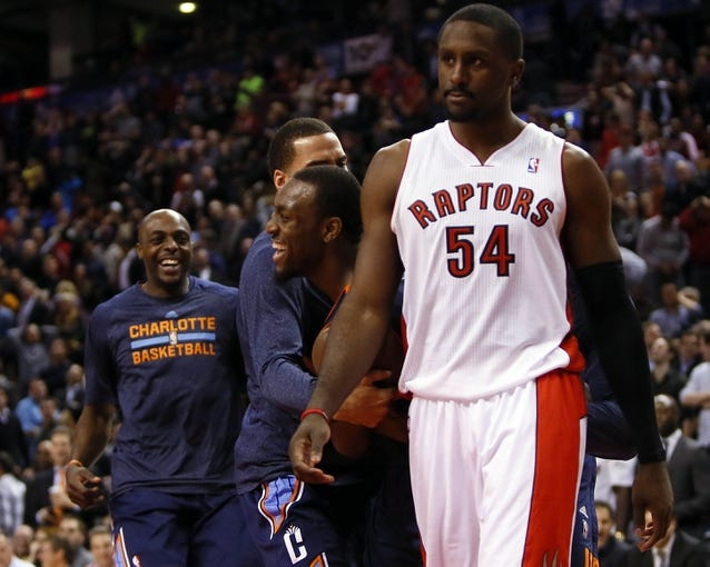 Dec 18, 2013; Toronto, Ontario, CAN; Charlotte Bobcats guard Kemba Walker (center) reacts behind Toronto Raptors forward Patrick Patterson (54) after scoring the game winning basket at the Air Canada Centre. Charlotte defeated Toronto 104-102 in overtime. Mandatory Credit: John E. Sokolowski-USA TODAY Sports