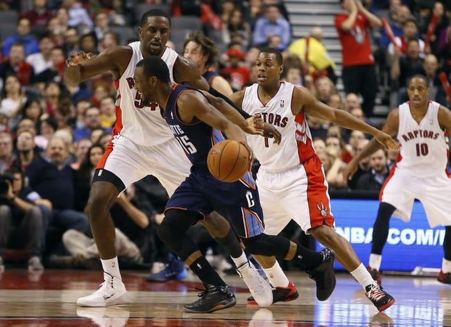 Dec 18, 2013; Toronto, Ontario, CAN; Charlotte Bobcats guard Kemba Walker (15) dribbles as Toronto Raptors forward Patrick Patterson (54) and Toronto Raptors guard Kyle Lowry (7) defend at the Air Canada Centre. Charlotte defeated Toronto 104-102 in overtime. Mandatory Credit: John E. Sokolowski-USA TODAY Sports
