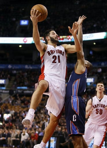 Dec 18, 2013; Toronto, Ontario, CAN; Toronto Raptors guard Greivis Vasquez (21)  goes up to make a basket as Charlotte Bobcats guard Ramon Sessions (7) defends at the Air Canada Centre. Charlotte defeated Toronto 104-102 in overtime. Mandatory Credit: John E. Sokolowski-USA TODAY Sports