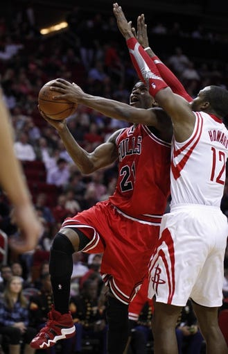 Dec 18, 2013; Houston, TX, USA; Chicago Bulls shooting guard Jimmy Butler (21) shoots against Houston Rockets power forward Dwight Howard (12) during the third quarter at Toyota Center. Mandatory Credit: Andrew Richardson-USA TODAY Sports