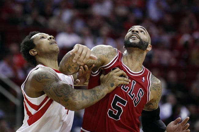 Dec 18, 2013; Houston, TX, USA; Houston Rockets power forward Greg Smith (4) and Chicago Bulls power forward Carlos Boozer (5) fight for the rebound during the third quarter at Toyota Center. Mandatory Credit: Andrew Richardson-USA TODAY Sports