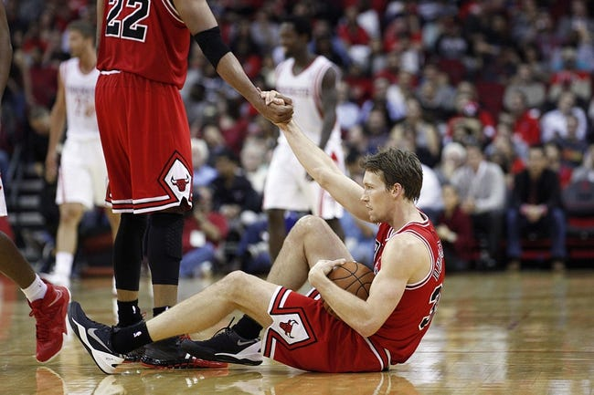 Dec 18, 2013; Houston, TX, USA; Chicago Bulls small forward Mike Dunleavy (34) is helped up by power forward Taj Gibson (22) during the fourth quarter against the Houston Rockets at Toyota Center. Mandatory Credit: Andrew Richardson-USA TODAY Sports