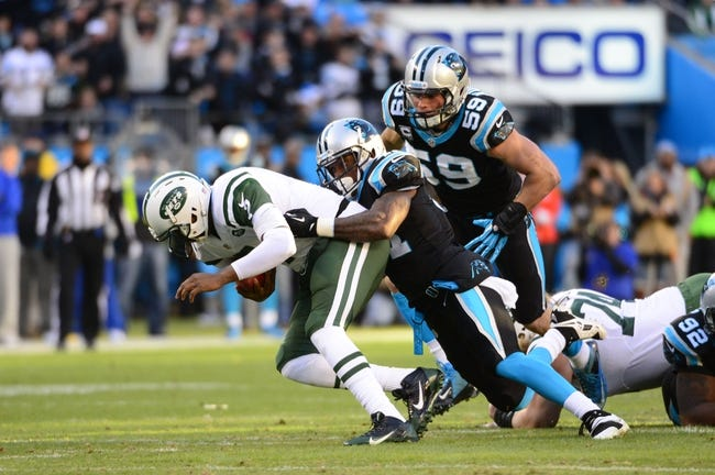 Dec 15, 2013; Charlotte, NC, USA; New York Jets quarterback Geno Smith (7) is sacked by Carolina Panthers cornerback Captain Munnerlyn (41) as middle linebacker Luke Kuechly (59) helps defend in the first quarter at Bank of America Stadium. Mandatory Credit: Bob Donnan-USA TODAY Sports