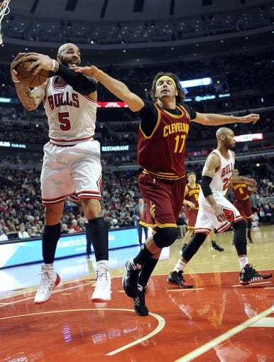 Dec 21, 2013; Chicago, IL, USA; Chicago Bulls power forward Carlos Boozer (5) and Cleveland Cavaliers center Anderson Varejao (17) go for the ball during the first quarter at the United Center. Mandatory Credit: David Banks-USA TODAY Sports