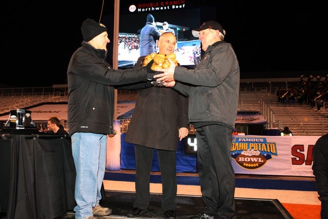 Dec 21, 2013; Boise, ID, USA;  Idaho Potato Commision CEO and president Frank Muir and ESPN Famous Idaho Potato Bowl executive director Kevin McDonald present the trophy  to San Diego State Aztecs head coach Rocky Long during the celebration of the Aztecs win at the Famous Idaho Potato Bowl over the Buffalo Bulls at Bronco Stadium. San Diego defeated Buffalo 49-24. Mandatory Credit: Brian Losness-USA TODAY Sports
