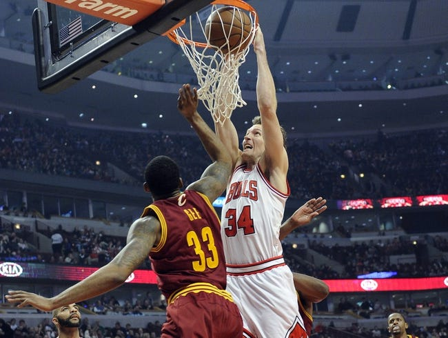 Dec 21, 2013; Chicago, IL, USA;  Chicago Bulls small forward Mike Dunleavy (34) dunks over Cleveland Cavaliers small forward Alonzo Gee (33) during the second half at the United Center. T'he Chicago Bulls defeated the Cleveland Cavaliers 100-84. Mandatory Credit: David Banks-USA TODAY Sports