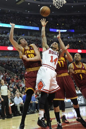 Dec 21, 2013; Chicago, IL, USA; Chicago Bulls point guard D.J. Augustin (14) shoots over Cleveland Cavaliers shooting guard Sergey Karasev (10) during the second half at the United Center. T'he Chicago Bulls defeated the Cleveland Cavaliers 100-84. Mandatory Credit: David Banks-USA TODAY Sports