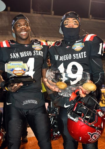 Dec 21, 2013; Boise, ID, USA; San Diego State Aztecs running back Adam Muema (4) and running back Donnel Pumphrey (19) hold trophies after the Idaho Potato Bowl against the Buffalo Bulls at Bronco Stadium. San Diego defeated Buffalo 49-24. Mandatory Credit: Brian Losness-USA TODAY Sports