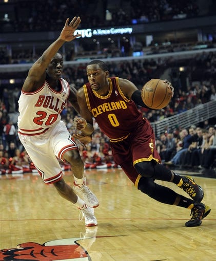 Dec 21, 2013; Chicago, IL, USA; Cleveland Cavaliers shooting guard C.J. Miles (0) drives to the basket and is defended by Chicago Bulls small forward Tony Snell (20) during the first quarter at the United Center. Mandatory Credit: David Banks-USA TODAY Sports