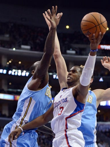 Dec 21, 2013; Los Angeles, CA, USA;  Los Angeles Clippers point guard Chris Paul (3) makes a shot past Denver Nuggets center Timofey Mozgov (25) and power forward J.J. Hickson (7) in the second half of the game at Staples Center. The Clippers won 112-91. Mandatory Credit: Jayne Kamin-Oncea-USA TODAY Sports