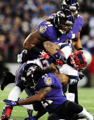 Dec 22, 2013; Baltimore, MD, USA; New England Patriots running back Stevan Ridley (22) gets tackled by Baltimore Ravens cornerback Lardarius Webb (21) and linebacker Courtney Upshaw (91) at M&T Bank Stadium. Mandatory Credit: Evan Habeeb-USA TODAY Sports