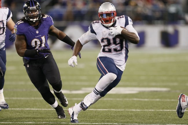 Dec 22, 2013; Baltimore, MD, USA; New England Patriots running back LaGarrette Blount (29) runs past Baltimore Ravens linebacker Courtney Upshaw (91) at M&T Bank Stadium. Mandatory Credit: Mitch Stringer-USA TODAY Sports