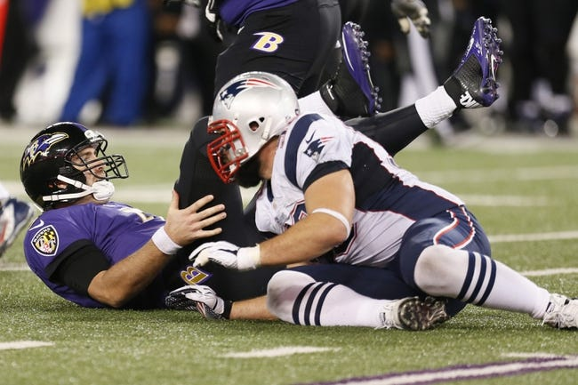 Dec 22, 2013; Baltimore, MD, USA; Baltimore Ravens quarterback Joe Flacco (5) sacked by New England Patriots linebacker Rob Ninkovich (50) at M&T Bank Stadium. Mandatory Credit: Mitch Stringer-USA TODAY Sports