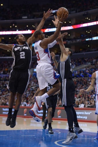 Dec 16, 2013; Los Angeles, CA, USA; Los Angeles Clippers guard Chris Paul (3) is defended by San Antonio Spurs forwards Kawhi Leonard (2) and Jeff Ayres (11) at Staples Center. Mandatory Credit: Kirby Lee-USA TODAY Sports