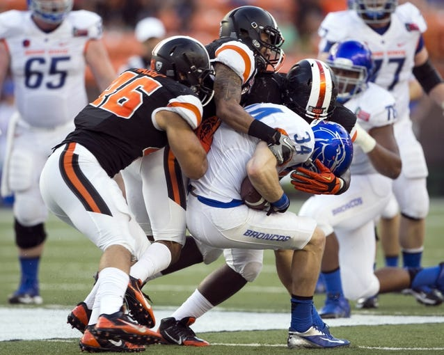 Dec 24, 2013; Honolulu, HI, USA; Boise State Broncos wide receiver Kirby Moore (34) gets stopped by Oregon State Beavers defensive tackle Edwin Delva (96), cornerback Sean Martin (6), and defensive tackle Mana Rosa (93) in the third quarter at the 2013 Hawaii Bowl at Aloha Stadium. Mandatory Credit: Marco Garcia-USA TODAY Sports