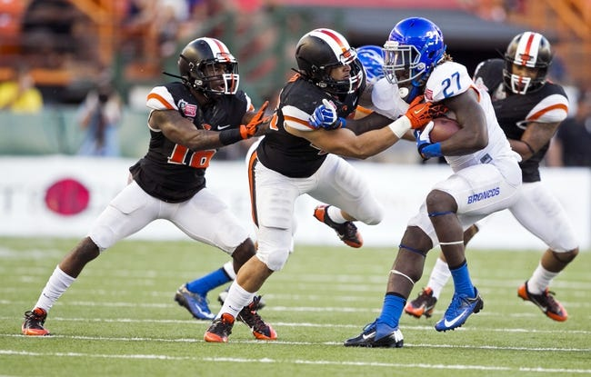 Dec 24, 2013; Honolulu, HI, USA; Boise State Broncos running back Jay Ajayi (27) gets tackled by Oregon State Beavers cornerback Rashaad Reynolds (16), linebacker Jabral Johnson (44), and linebacker Rommel Mageo (46) in the third quarter at the 2013 Hawaii Bowl at Aloha Stadium. Mandatory Credit: Marco Garcia-USA TODAY Sports