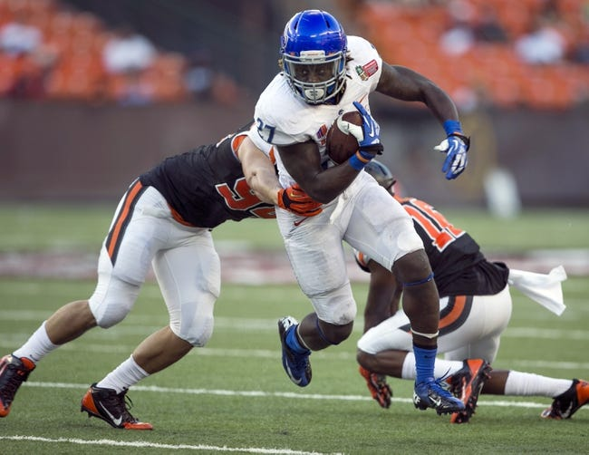 Dec 24, 2013; Honolulu, HI, USA; Boise State Broncos running back Jay Ajayi (27) runs through the tackle from Oregon State Beavers defensive end Devon Kell (94) in the third quarter at the 2013 Hawaii Bowl at Aloha Stadium. Mandatory Credit: Marco Garcia-USA TODAY Sports