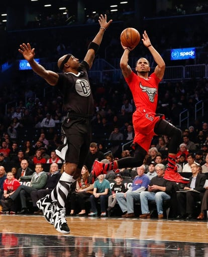 Dec 25, 2013; Brooklyn, NY, USA; Chicago Bulls point guard D.J. Augustin (right) shoots over Brooklyn Nets shooting guard Jason Terry (31) during the first quarter at Barclays Center. Mandatory Credit: Anthony Gruppuso-USA TODAY Sports