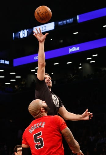 Dec 25, 2013; Brooklyn, NY, USA;  Brooklyn Nets power forward Mirza Teletovic (33) shoots over Chicago Bulls power forward Carlos Boozer (5) during the third quarter at Barclays Center. Chicago Bulls won 95-78.  Mandatory Credit: Anthony Gruppuso-USA TODAY Sports