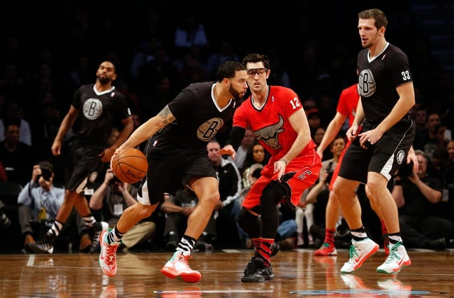 Dec 25, 2013; Brooklyn, NY, USA;  Brooklyn Nets point guard Deron Williams (8) drives past Chicago Bulls shooting guard Kirk Hinrich (12) during the first quarter at Barclays Center. Mandatory Credit: Anthony Gruppuso-USA TODAY Sports