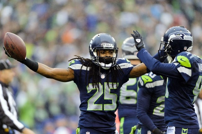 Dec 22, 2013; Seattle, WA, USA; Seattle Seahawks cornerback Richard Sherman (25) and cornerback Byron Maxwell (41) celebrate after Sherman intercepted the ball thrown by Arizona Cardinals quarterback Carson Palmer (not pictured) during the game at CenturyLink Field. Arizona defeated Seattle 17-10. Mandatory Credit: Steven Bisig-USA TODAY Sports