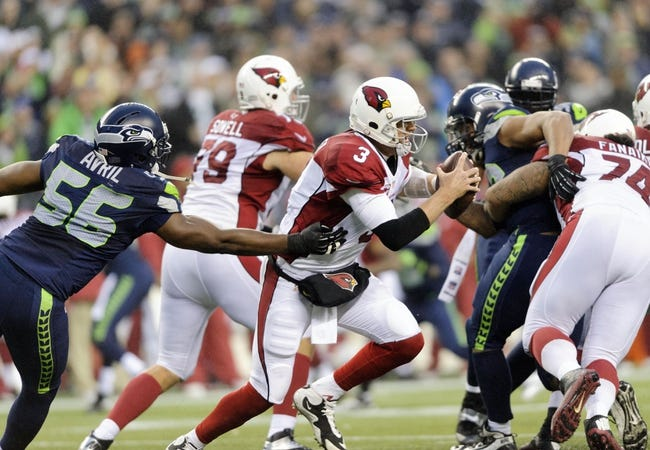 Dec 22, 2013; Seattle, WA, USA; Arizona Cardinals quarterback Carson Palmer (3) moves out of the pocket away from Seattle Seahawks defensive end Cliff Avril (56) during the game at CenturyLink Field. Arizona defeated Seattle 17-10. Mandatory Credit: Steven Bisig-USA TODAY Sports