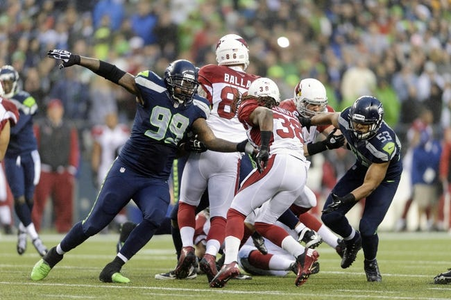 Dec 22, 2013; Seattle, WA, USA; Seattle Seahawks defensive tackle Tony McDaniel (99) and outside linebacker Malcolm Smith (53) chase Arizona Cardinals running back Andre Ellington (38) during the game at CenturyLink Field. Arizona defeated Seattle 17-10. Mandatory Credit: Steven Bisig-USA TODAY Sports