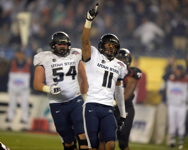 Dec 26, 2013; San Diego, CA, USA; Utah State Aggies receiver Brandon Swindall (11) celebrates with lineman Jamie Markosian (54) after scoring on a 5-yard touchdown pass in the third quarter during the 2013 Poinsettia Bowl against the Northern Illinois Huskies at Qualcomm Stadium. Utah State defeated Northern Illinois 21-14. Mandatory Credit: Kirby Lee-USA TODAY Sports