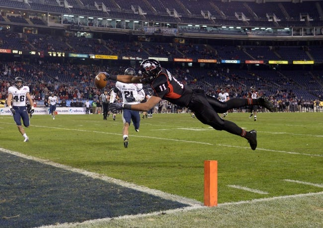 Dec 26, 2013; San Diego, CA, USA; Northern Illinois Huskies receiver Juwan Brescacin (11) leaps into the end zone to score on a 15-yard touchdown reception in the fourth quarter against the Utah State Aggies in the 2013 Poinsettia Bowl at Qualcomm Stadium. Mandatory Credit: Kirby Lee-USA TODAY Sports