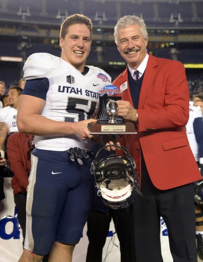 Dec 26, 2013; San Diego, CA, USA; Utah State Aggies linebacker Jake Doughty (51) is presented the most valuable defensive player trophy by San Diego bowl game association president Bill Geppert after the 2013 Poinsettia Bowl against the Northern Illinois Huskies at Qualcomm Stadium. Mandatory Credit: Kirby Lee-USA TODAY Sports