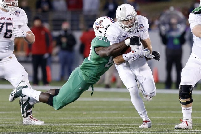 Dec 27, 2013; Annapolis, MD, USA; Maryland Terrapins quarterback C.J. Brown (16) runs with the ball as Marshall Thundering Herd defensive lineman Alex Bazzie (53) makes the tackle in the third quarter during the 2013 Military Bowl at Navy Marine Corps Memorial Stadium. The Thundering Herd won 31-20. Mandatory Credit: Geoff Burke-USA TODAY Sports